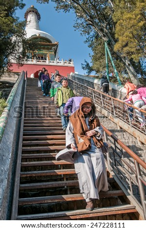 BEIJING, CHINA - MARCH 28: Buddhist monk on a stairs to Bai Ta (White Pagoda) stupa and ShanYin Pavilion in Buddhist Yong'An (Temple of Everlasting Peace) in Beihai Park on March 28, 2013 in Beijing - stock photo