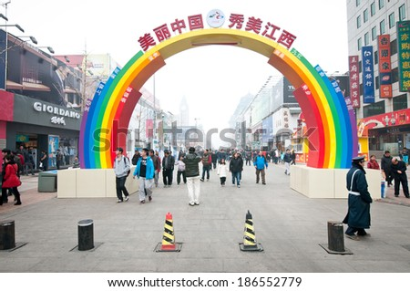 BEIJING, CHINA - MARCH 30: Chinese people and tourist walks through rainbow shape gate at famous Wangfujing pedestrian street on March 30, 2013 in Beijing - stock photo