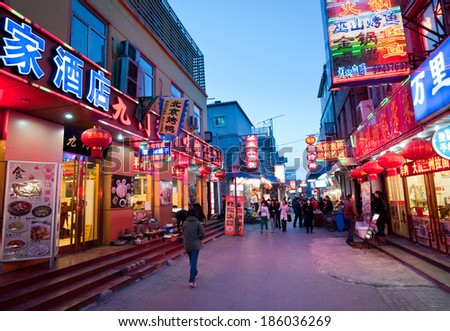 BEIJING, CHINA - MARCH 27:  Chinese people walks next to restaurants on one of the parallel street to famous Qianmen Dajie pedestrian commercial street on March 27, 2013 in Beijing - stock photo
