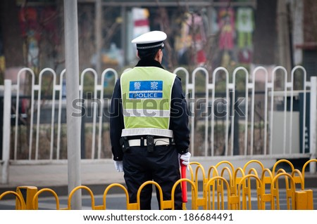 BEIJING, CHINA - MARCH 31: Chinese traffic police officer stands on duty on the street on March 31, 2013 in Beijing - stock photo