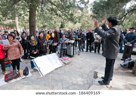 BEIJING, CHINA - MARCH 28: concertmaster stands in front of group of people in Jingshan Park on March 28, 2013 in Beijing - stock photo
