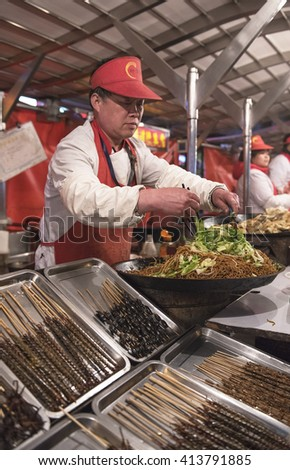 BEIJING, CHINA - 22 MARCH, 2016: Food vendors at the Donghuamen Night Market near Wangfujing Street on March 22, 2016 in Beijing, China. It is a 700-year-old street.