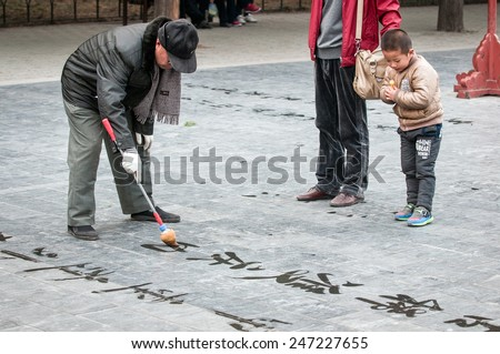 BEIJING, CHINA - MARCH 26: Kid looking on Chinese letters written by old man practising calligraphy in Temple of Heaven park area on March 26, 2013 in Beijing - stock photo