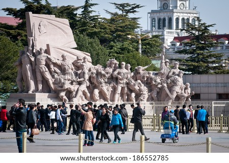 BEIJING, CHINA - MARCH 27: tourists stands in front of revolutionary statu next to Mausoleum of Mao Zedong at Tiananmen Square on March 27, 2013 in Beijing - stock photo