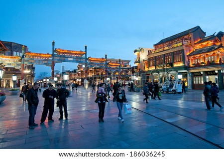 BEIJING, CHINA - MARCH 27:  tourists walks in front paifang archway at famous Qianmen Dajie pedestrian commercial street on March 27, 2013 in Beijing - stock photo