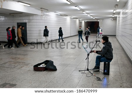 BEIJING, CHINA - MARCH 30: Young Chinese man plays guitar and singing for money in underground passage on March 30, 2013 in Beijing - stock photo