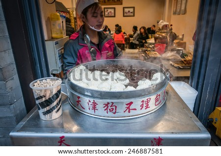 BEIJING, CHINA - MARCH 27: young woman selleing Xiaolongbao dumplings in restaurant at one of perpendicular street to famous Qianmen Dajie pedestrian commercial street on March 27, 2013 in Beijing - stock photo
