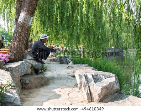BEIJING, CHINA - MAY 18, 2016. Elderly Chinese man sitting on his haunches on the stone and reading a newspaper against the backdrop of a tree with lush foliage and lake