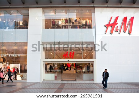 BEIJING, CHINA - NOV. 17, 2014: People is seen around a H & M store; H & M, a Swedish multinational retail-clothing company, exists in 55 countries and as of 2013 employed around 116,000 people. - stock photo