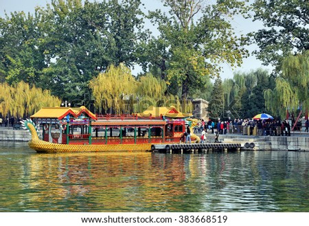 BEIJING, CHINA  ?? NOVEMBER 10, 2008: tourists taking a typical boat to the Summer Palace at the Kunming lake  - stock photo