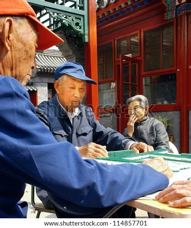 BEIJING, CHINA - OCT. 12, 2011 : unidentified eldery people playing a game of dominos on oct, 12, 2011 Beijing .By 2015 there will be 220 million people more than 60 years old in China - stock photo