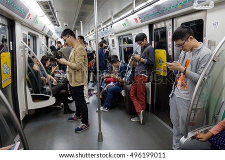 BEIJING, CHINA -OCTOBER 1, 2016: Passengers use their mobile phones in a subway train. Mobile phones and tablets are used for people to entertain and view information when taking public transportation