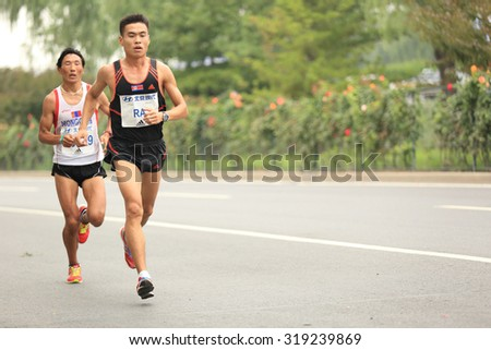BEIJING,CHINA - SEPTEMBER 20:Marathon runner running on city road  at the 34th Beijing Hyundai Beijing Marathon SEPTEMBER 20,2015 in  Being,China