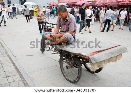 BEIJING - CIRCA JUNE, 2015: Rickshaw Man uses a smartphone while on the famous Panjiayuan Antique Market - one of the best antiques market in China. Area shopping area of 48 500 m2 - stock photo