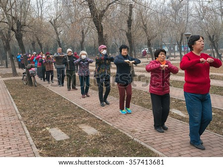 BEIJING - DEC 8: mask-covered Beijing residents doing outdoor exercise on December 8, 2015 in Beijing, China.The Chinese government issued the historical first Red Alert on air pollution on this day.