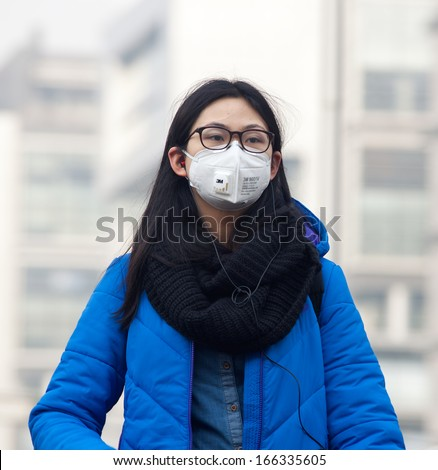 BEIJING-DEC 8: Woman with face mask is seen on Dec 8, 2013 in Beijing, China.  104 cities in China suffered from severe air pollution on Dec 7, with Beijing among that hit the hardest - stock photo