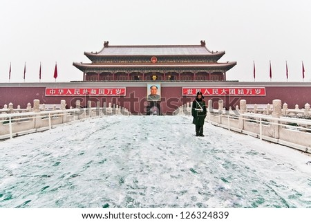BEIJING - JANUARY20 Snowflakes were flying, a soldier stood on the Tiananmen rostrum in Beijing in January 20, 2013, china. Guarded. Chairman Mao Zedong in China is still worship. - stock photo