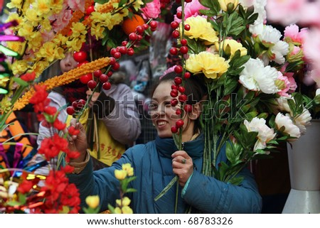 BEIJING - JANUARY 31: Young Chinese woman selling flowers at the Spring Festival Fair in Ditan Park in Beijing, January 31, 2009. The fair marked the beginning  or the Chinese Lunar New Year. - stock photo