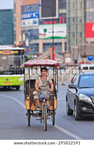 BEIJING-JULY 10, 2015. An electric motorized rickshaw. In Chinese cities rickshaws are still a popular and affordable transport mode for short distances, currently they are all electric motorized. 