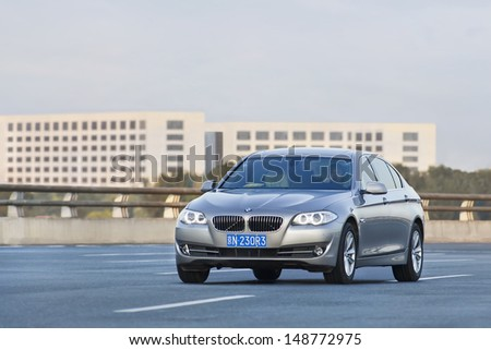 BEIJING-JULY 5. BMW 5 series long wheelbase riding at the expressway at dusk. BMW�¢??s sales in China increased 15.0% compared with the same period (first six months) last year. Beijing, July 5, 2013. - stock photo