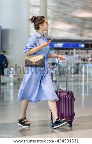 BEIJING-JULY 13, 2016. Fashionable young woman girl with suitcase walks at Beijing Capital International Airport, Terminal 3, with 986,000 m2 the second largest airport terminal building in the world.