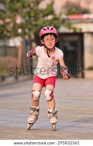 BEIJING-JULY 10, 2015. Girl practicing inline skating. Although Ping-Pong, basketball and badminton are China's top sports, last decade inline skating became increasingly popular among Chinese youth. - stock photo