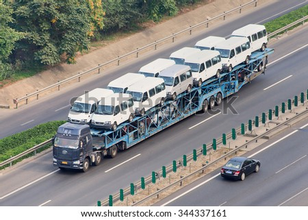BEIJING-JULY 10, 2015. Oversized car carrier. These illegal car trailers have lengths up to 40m and carry often over 20 cars while a normal car carrier would likely carry no more than 8 to 10 cars. - stock photo