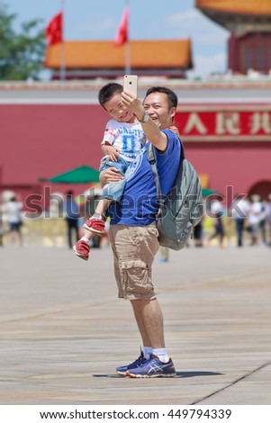 BEIJING-JUNE 11, 2016. Cheerful father and son take selfie on sunny Tiananmen Square, one of the world's largest squares (440,500 m2). It has great cultural significance as place of historical events. - stock photo