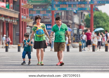 BEIJING-JUNE 9, 2015. Chinese couple with child. China's one-child policy, initiated late 1970s - early 1980s was to limit families have one child to reduce growth rate of China's enormous population. - stock photo