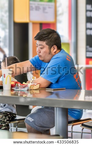 BEIJING-JUNE 5, 2016. Man at MacDonald. Fast food culture in China has caused common overweight. The average waistline of Chinese urban males has grown from 63.5cm to 76.2cm in less than 30 years. - stock photo