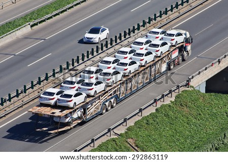 BEIJING-JUNE 30, 2015. Over sized car carrier. These illegal car trailers have lengths up to 40m and carry often over 20 cars while a normal car carrier would likely carry no more than 8 to 10 cars. - stock photo