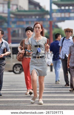 BEIJING-JUNE 9, 2015. Young attractive woman with a snack in her hand on a zebra path. Over 27 and unmarried females in China are labelled as leftover women, but many of them are happy being single. - stock photo