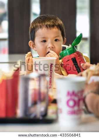 BEIJING-JUNE 5, 2016. Young boy at MacDonald. Chinese children are often spoiled with fast food, which has bad effects. Their body shapes become corpulent and they are stressed with health problems. - stock photo