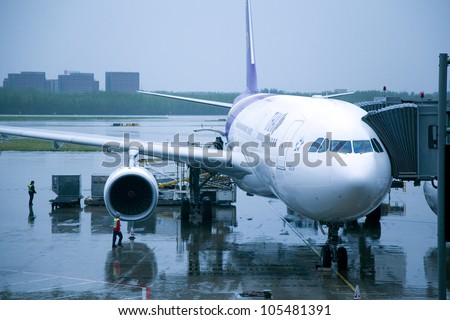 BEIJING - MAR 22:Thai Airways aircraft docking at Beijing Capital Airport on March 16, 2012. The airport registered 488,495 aircraft movements (take-offs + landings), ranked 10th in the world. - stock photo