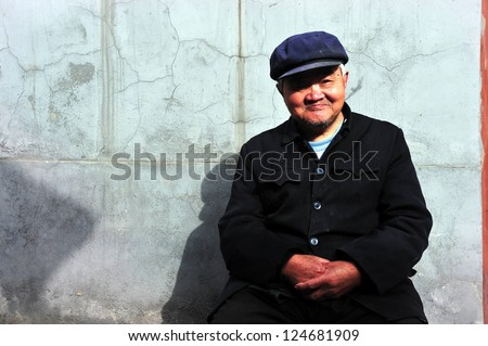 BEIJING - MARCH 12:An old Chinese man sits outside his home in Hutong (old neighbourhood) on March 12 2009 in Beijing, China.The average life expectancy among Chinese men is 72 years