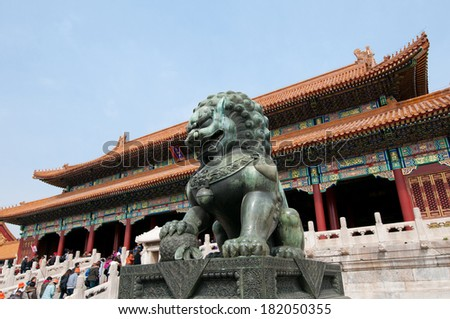 BEIJING - MARCH 28: Tourists passing bronze lion guardian statue in front of Gate of Supreme Harmony in Forbidden City on March 28, 2013 in Beijing