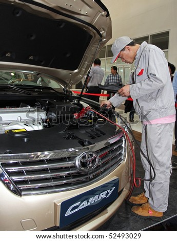 BEIJING - MAY 2: An employee works on a Toyota Camry at the 2010 Beijing International Automotive Exhibition (Auto China 2010) on May 2, 2010 in Beijing, China. - stock photo