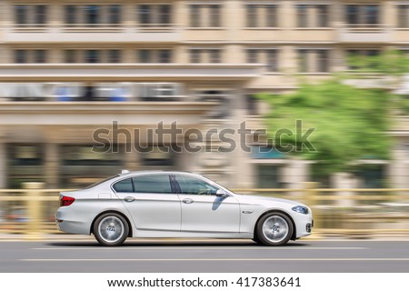 BEIJING-MAY 4, 2016. BMW 5 series L on the road. BMW sales will be hit in 2016 by cut-throat competition, slowing Chinese economy and recent government crackdown on graft and conspicuous consumption. - stock photo