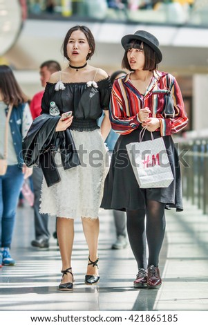 BEIJING-MAY 15, 2016. Fashionable girls in shopping mall. Chicana's economy, boosted by middle class wealth, undergoes a significant shift in consumption, driven by a new wave of prosperous consumers. - stock photo