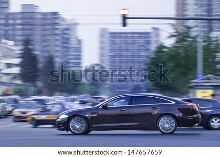 BEIJING-MAY 23. Jaguar XJ limousine in city center at twilight. Jaguar achieved its best ever global sales, with up 30% following strong market performances in UK, China and US. Beijing, May 23, 2013. - stock photo