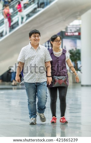 BEIJING-MAY 15, 2016. Overweight couple in shopping mall. The average waistline of Chinese urban males has gone from 63.5 cm in 1985 to 76.2 cm in 2012, growing by 20 percent over just 27 years.  - stock photo