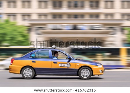 BEIJING-MAY 4, 2016. Taxi with bus on background. The number of Beijing taxis is larger than many other cities in the world. Data shows that in 2010 there were 66,646 taxis and 80,000 taxi drivers. - stock photo