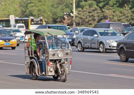 BEIJING-MAY 29, 2013. Tricycle motor taxi downtown. This small taxi is similar to Thailand Tuk Tuks, Philippines Tricycles and Vietnam Cyclo, cost 20 RMB short ride (3 KM), 5 RMB per KM afterwards.  - stock photo
