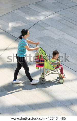 BEIJING-MAY 18, 2016. Woman with baby car in shopping mall. China is very concerned over an aging population and shrinking workforce and ended its one-child policy, allow couples having two children. - stock photo