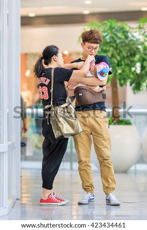 BEIJING-MAY 18, 2016. Young couple busy with baby feeding. China is very concerned over an aging population and shrinking workforce and ended its one-child policy, allow couples having two children. - stock photo