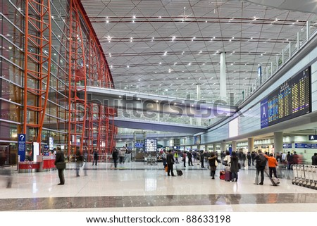 BEIJING - NOV. 10: Travelers pass through the arrival hall in Beijing Capital Airport Terminal 3 on Nov. 10, 2011 in Beijing, China. The airport registered 488,495 aircraft movements (take-offs and landings), ranked 10th in the world. - stock photo