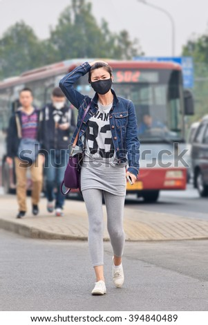 BEIJING-OCT. 19, 2014. Fashionable girl with face mask against smog. Beijing raised its smog alert to orange because air quality (concentration of PM2.5 small particles) became a human health threat. - stock photo