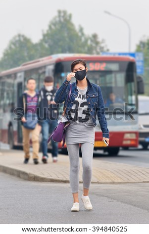 BEIJING-OCT. 19, 2014. Fashionable girl with face mask against smog. Beijing raised its smog alert to orange because air quality (concentration of PM2.5 small particles) became a human health threat.