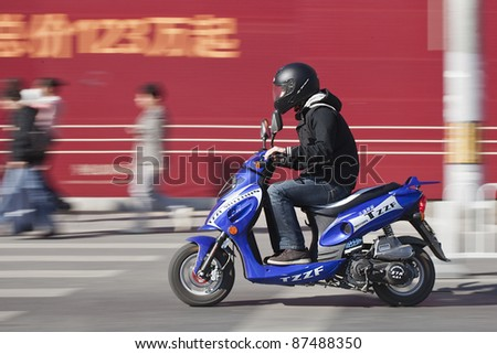 BEIJING - OCT. 25: Man rushes on a scooter in Beijing, Oct. 25, 2011. Currently, majority of Beijing residents prefer scooters instead of cars to avoid wasting time on congested streets. - stock photo