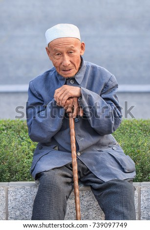 BEIJING-SEPTEMBER 4, 2015. Muslim senior in a park with a wooden stick. Currently, Muslims are a significant minority group in China. Hui Muslims are the majority, mainly concentration in Xinjiang.